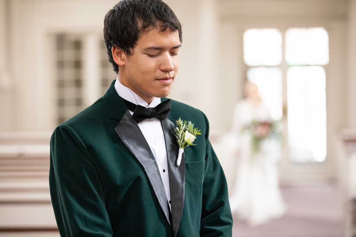 Groom waiting for bride during first look.
