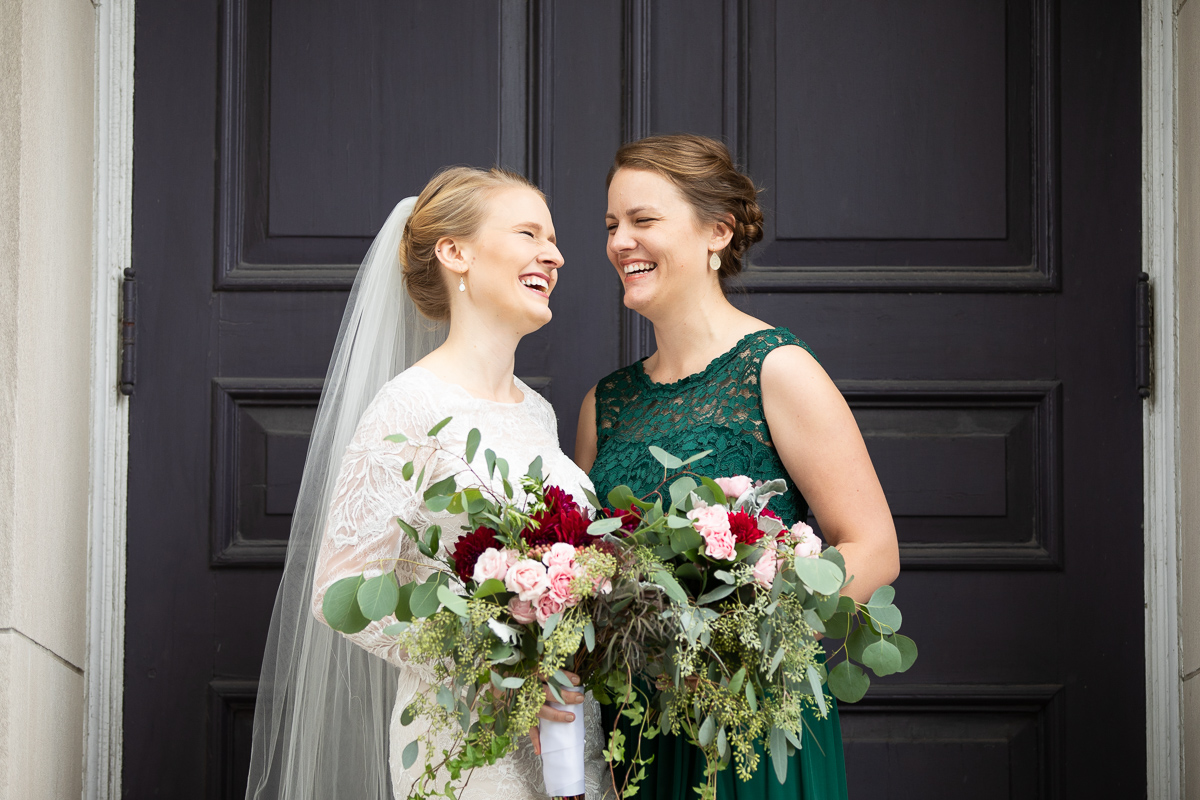 Bride and matron of honor laughing during formal photos.