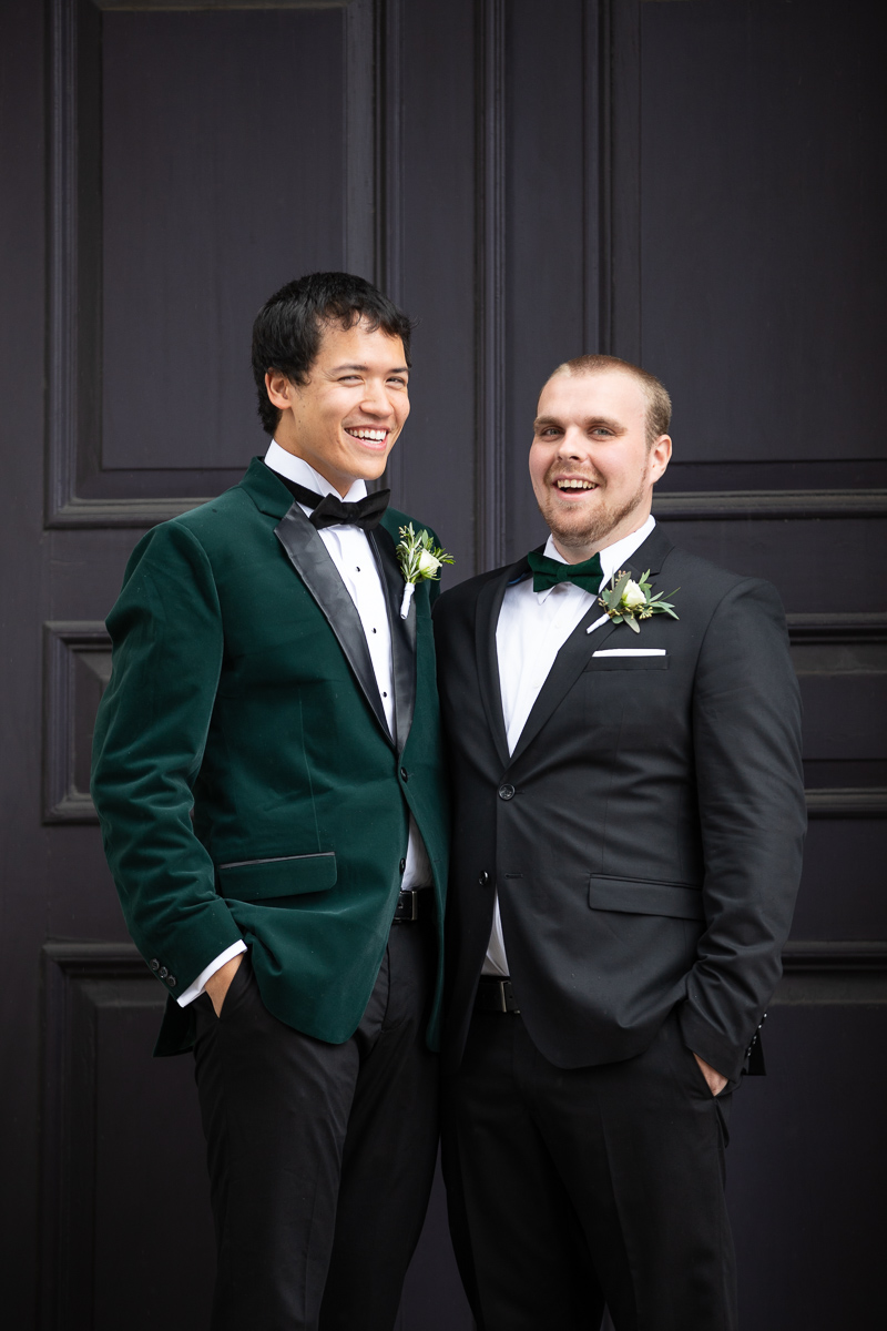 Groom and groomsman laughing during formal photos.