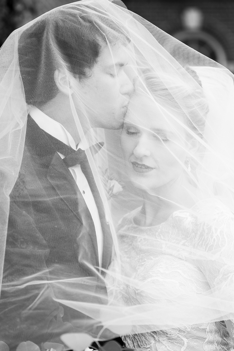 Black and white photo of bride and groom under veil.