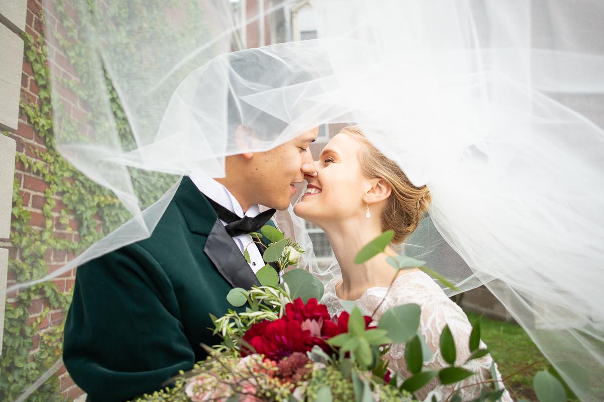 Bride and groom under veil.