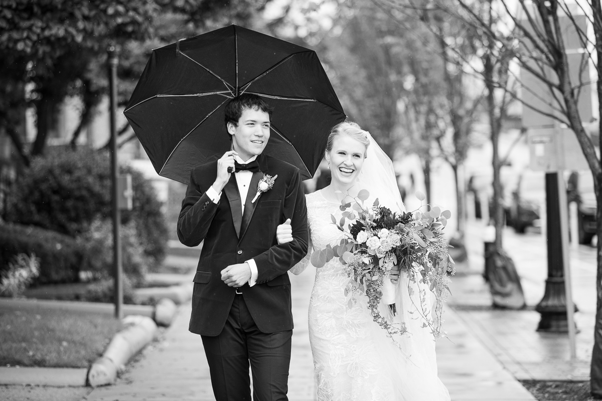 Bride and groom walking in downtown Boston in the rain.