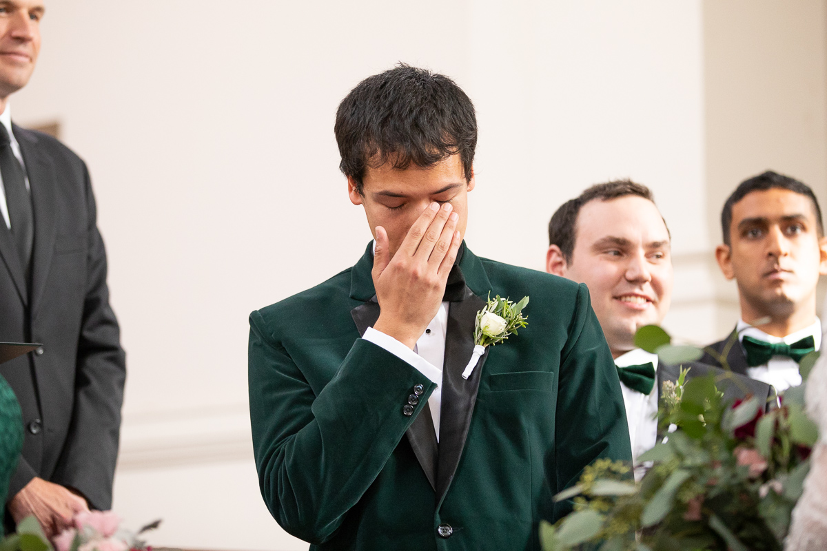 Groom crying while bride walks down the aisle.