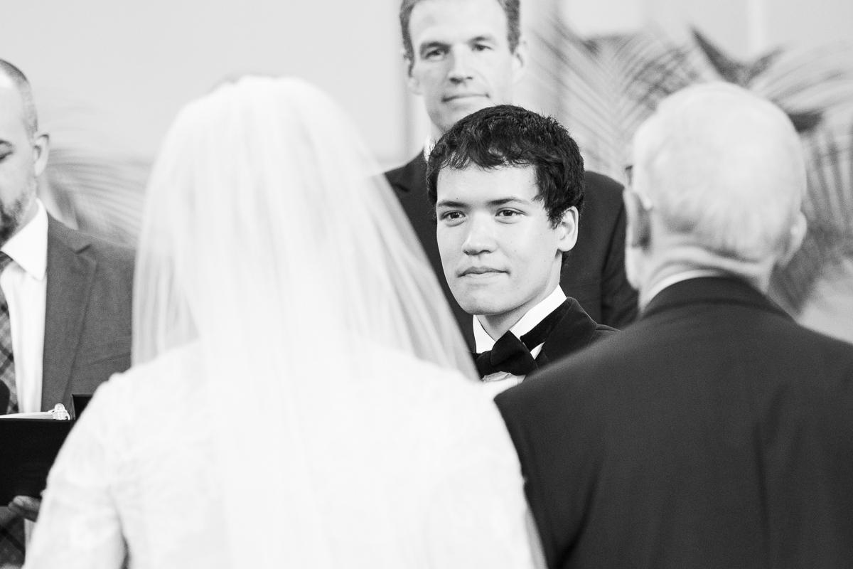 Groom looking at bride walk down the aisle.
