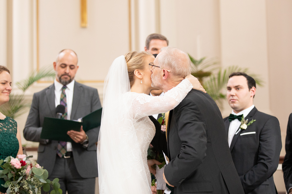 Bride's father giving bride a kiss at wedding ceremony.