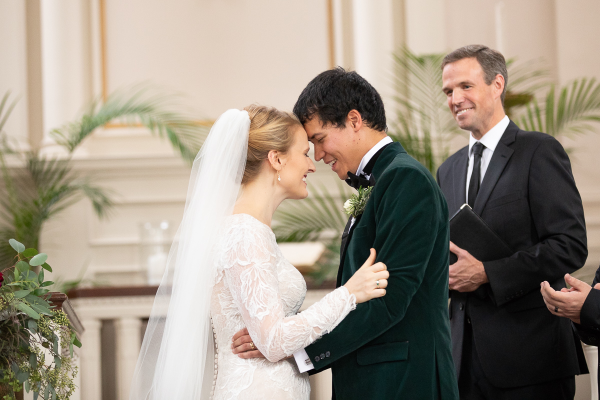 Bride and groom smiling after first kiss.