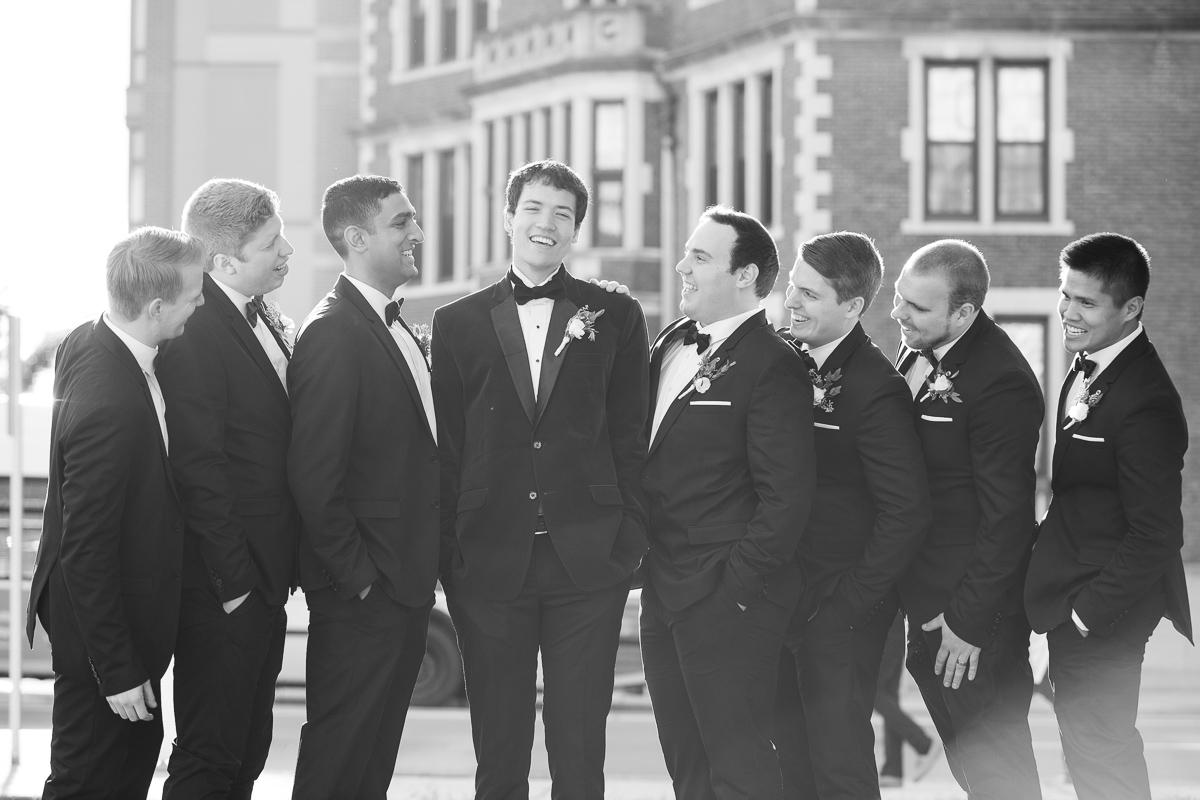 Groom and groomsmen laughing during Boston wedding.