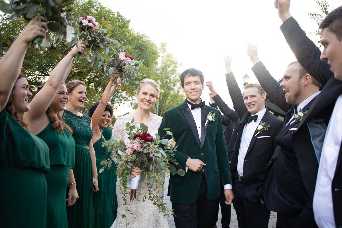 Bridal party cheering for bride and groom.