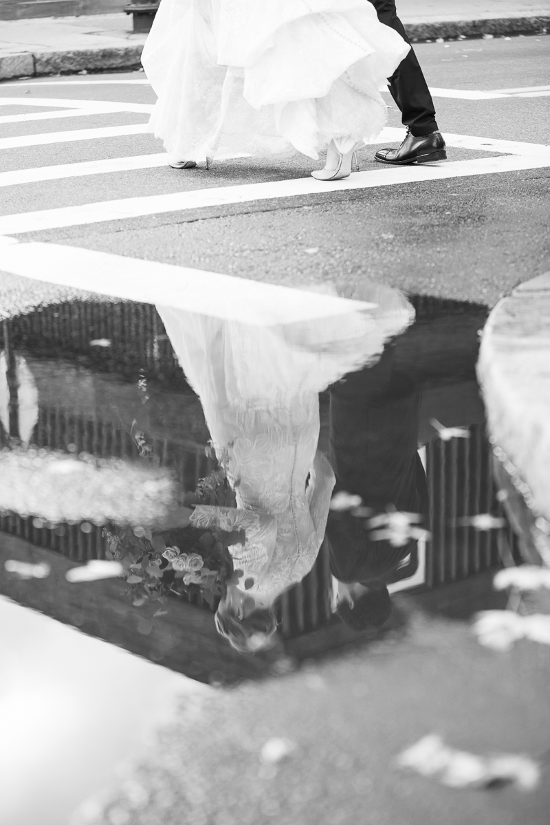 Reflection of bride and groom walking in Boston.