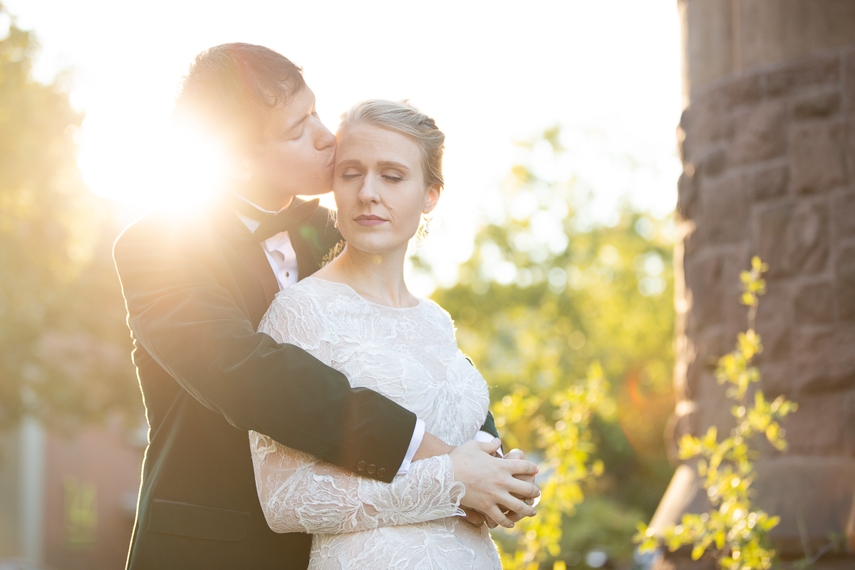 Groom giving bride a kiss at golden hour.