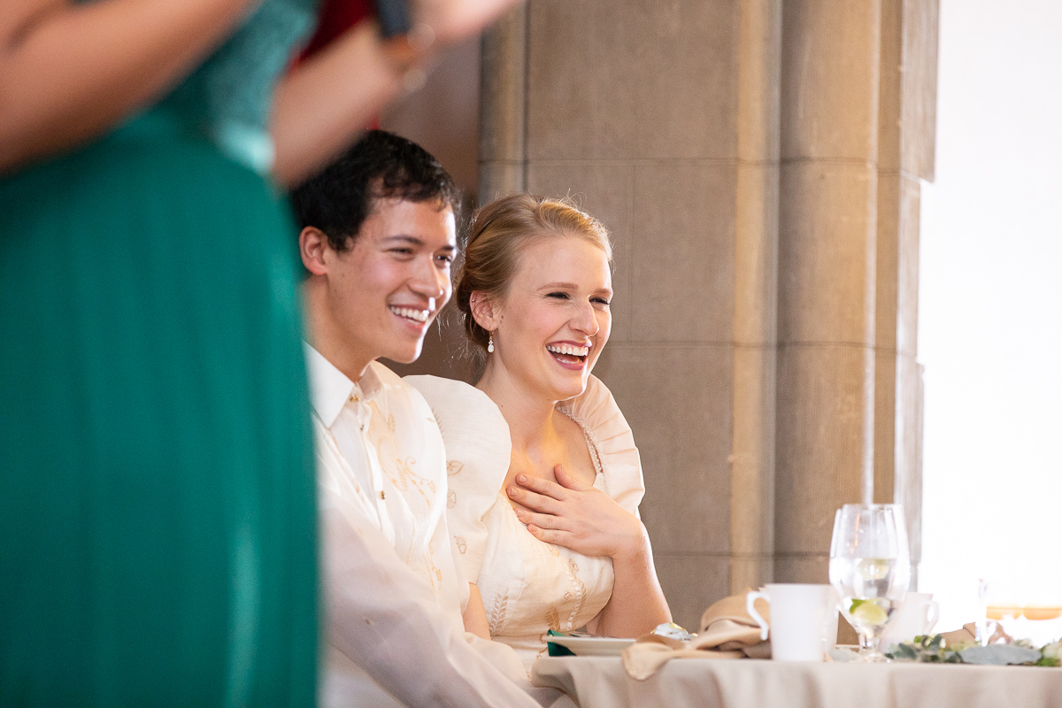 Bride and groom laughing during wedding toasts at reception.