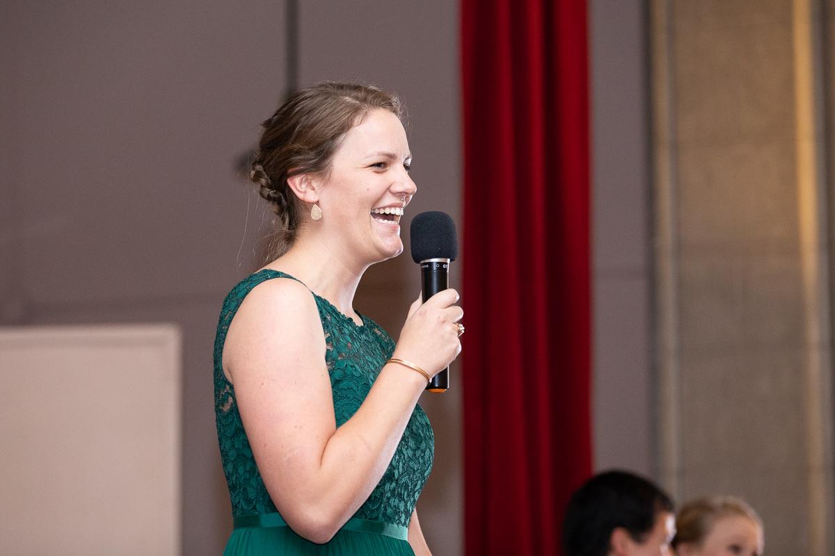 Matron of honor giving speech at reception.
