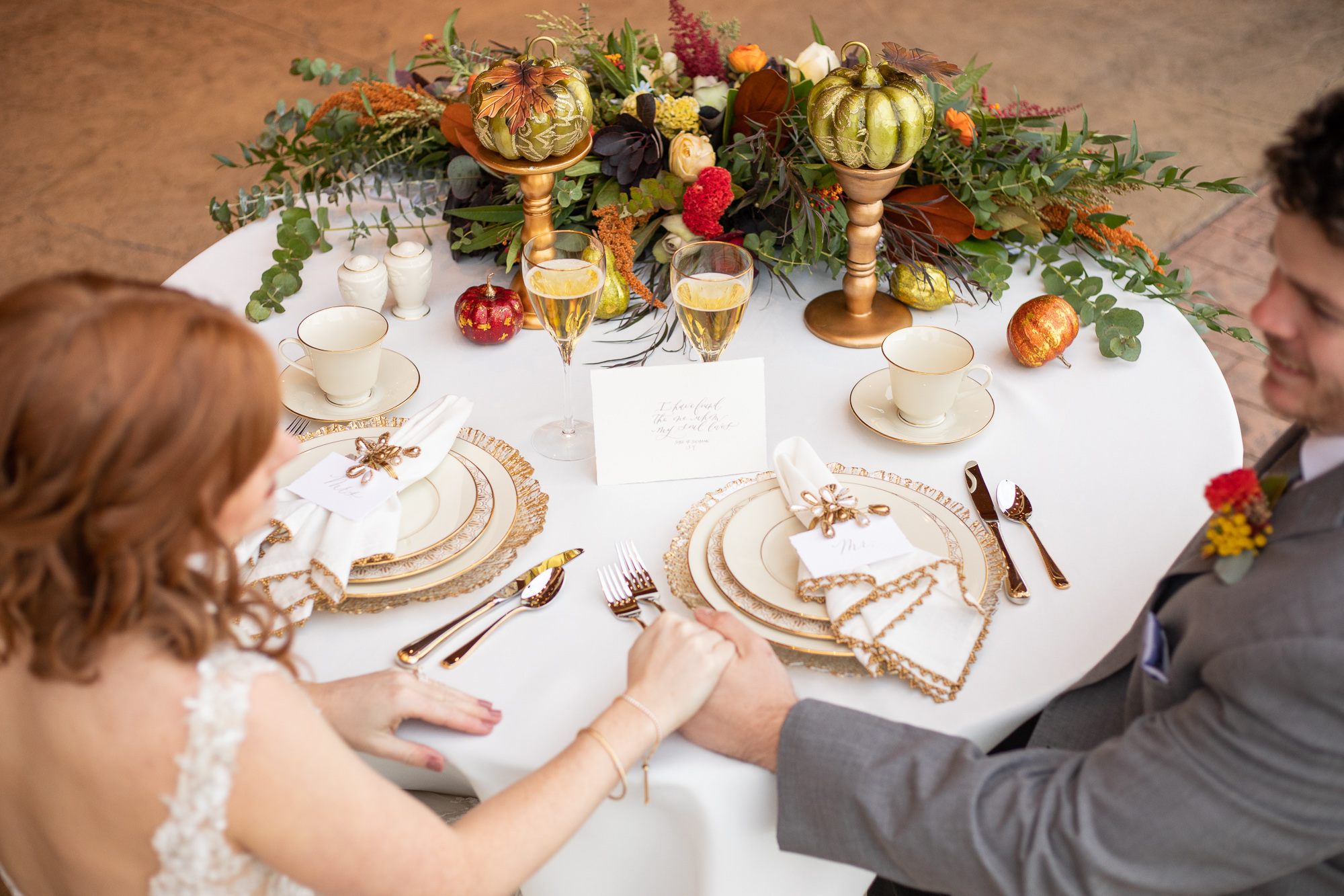 Bride and groom at autumn styled shoot sweetheart table.