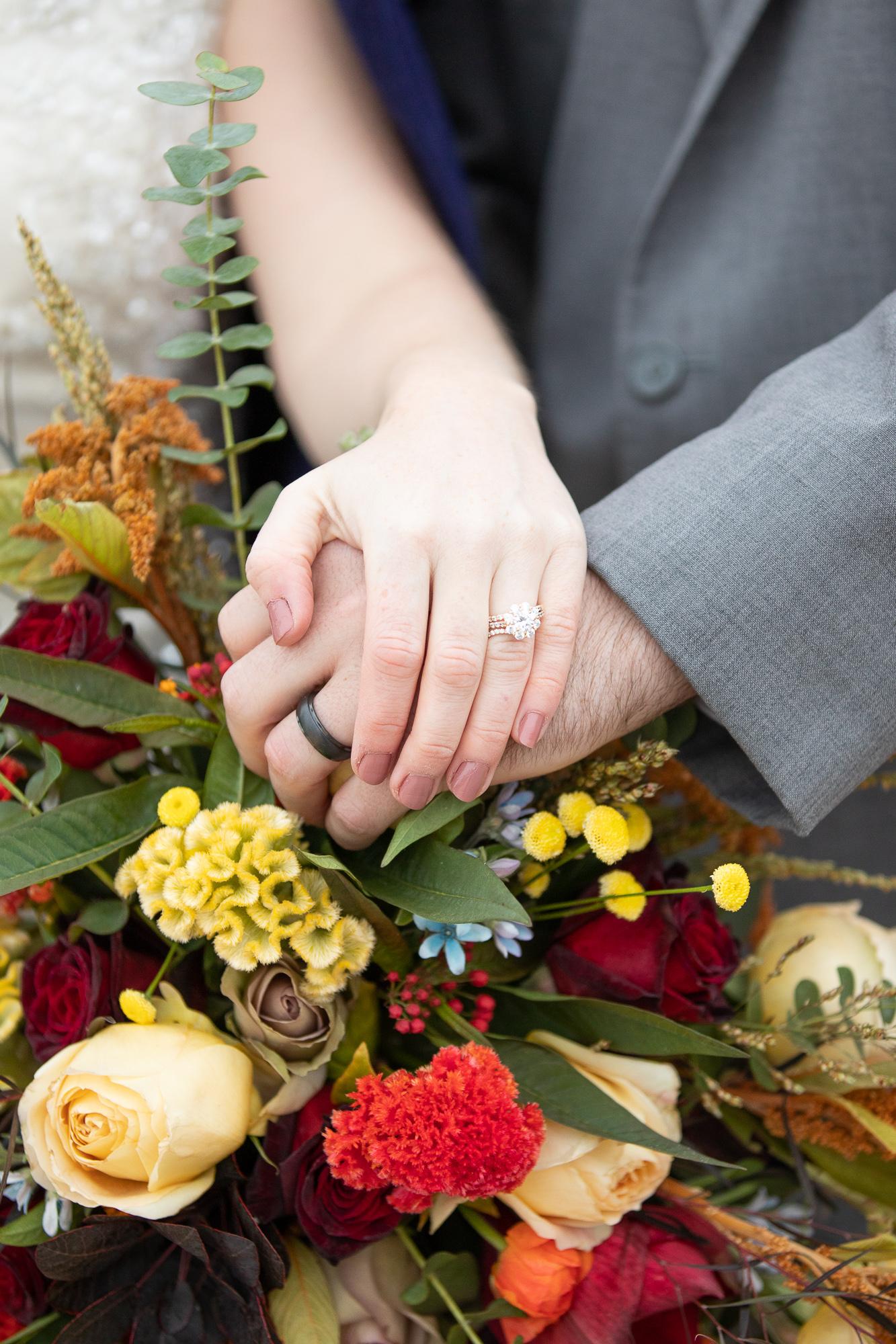 Bride and groom wearing Kimpel's Jewelers wedding rings on Posies by Pattie bridal bouquet.