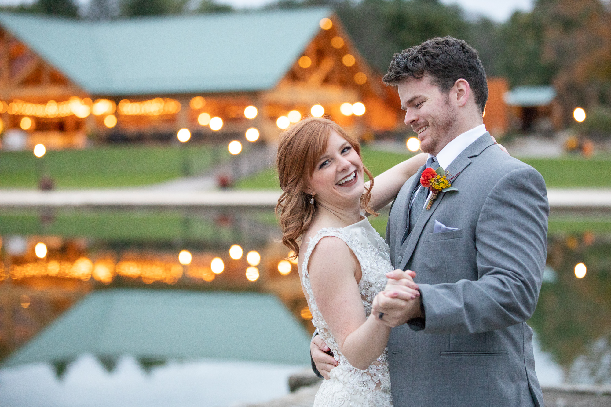 Bride and groom's first dance with lights on the water at The Gathering Place at Darlington Lake