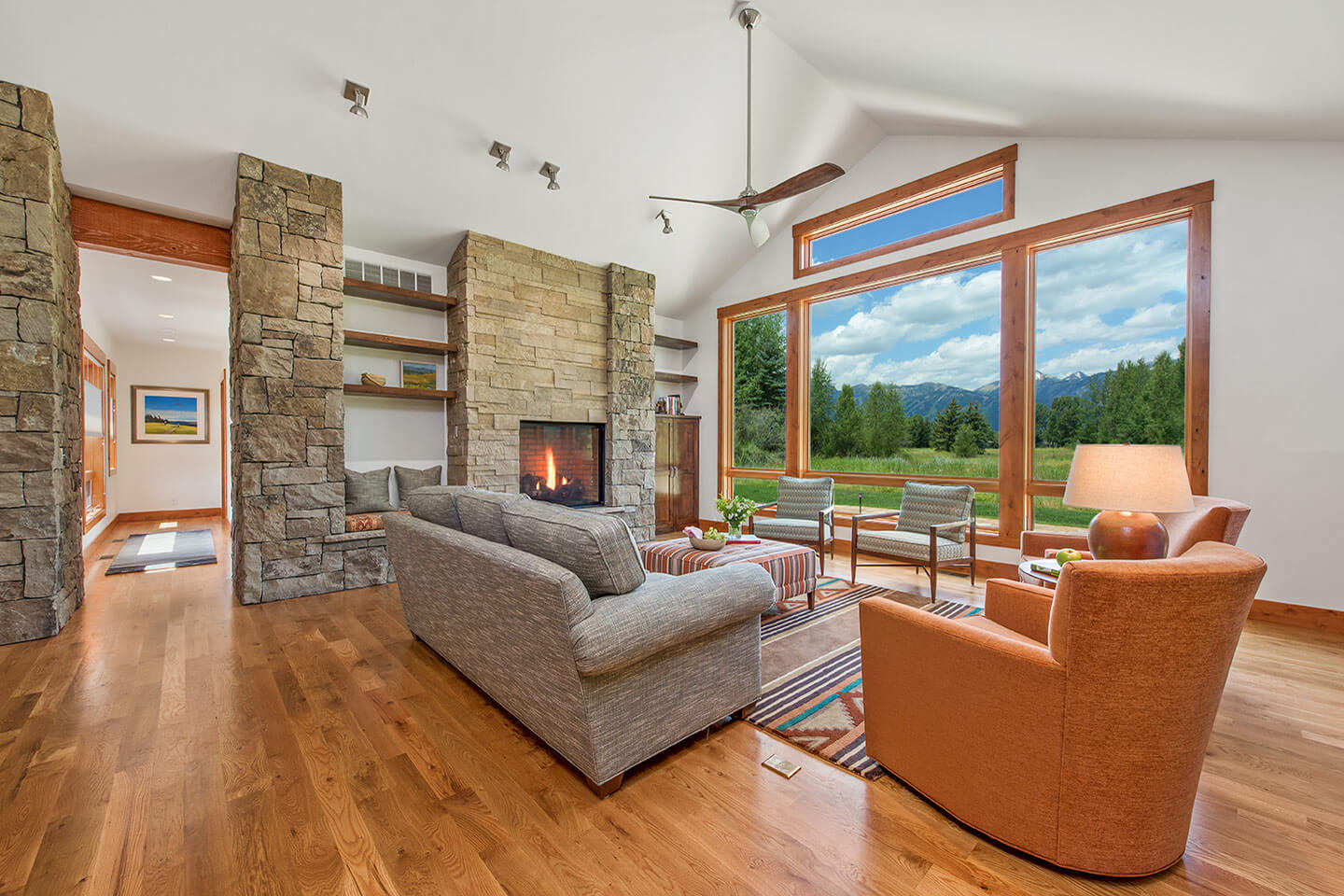Living room with native stone fireplace and wood flooring
