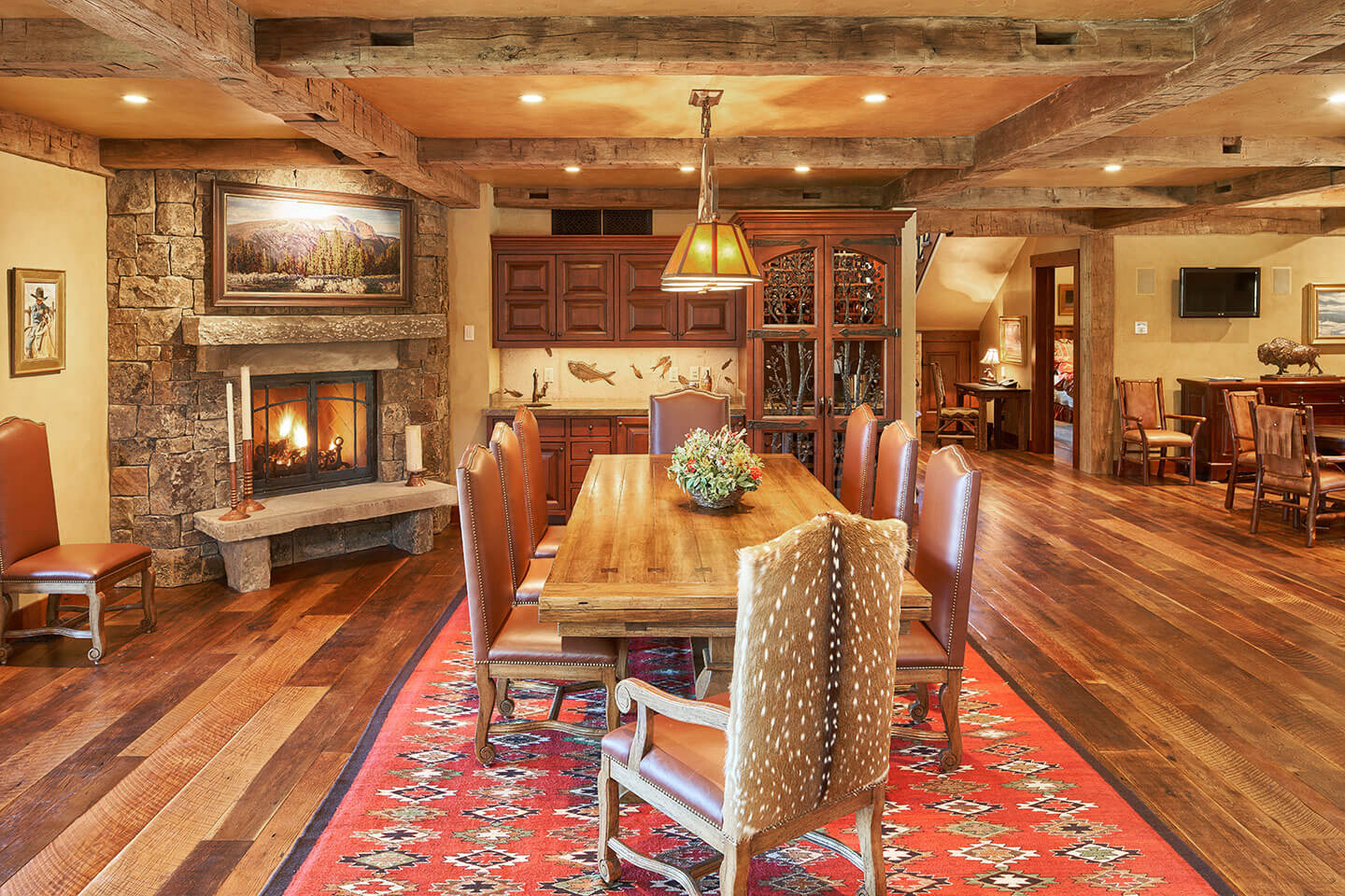 Dining room with wide plank flooring and rustic fireplace