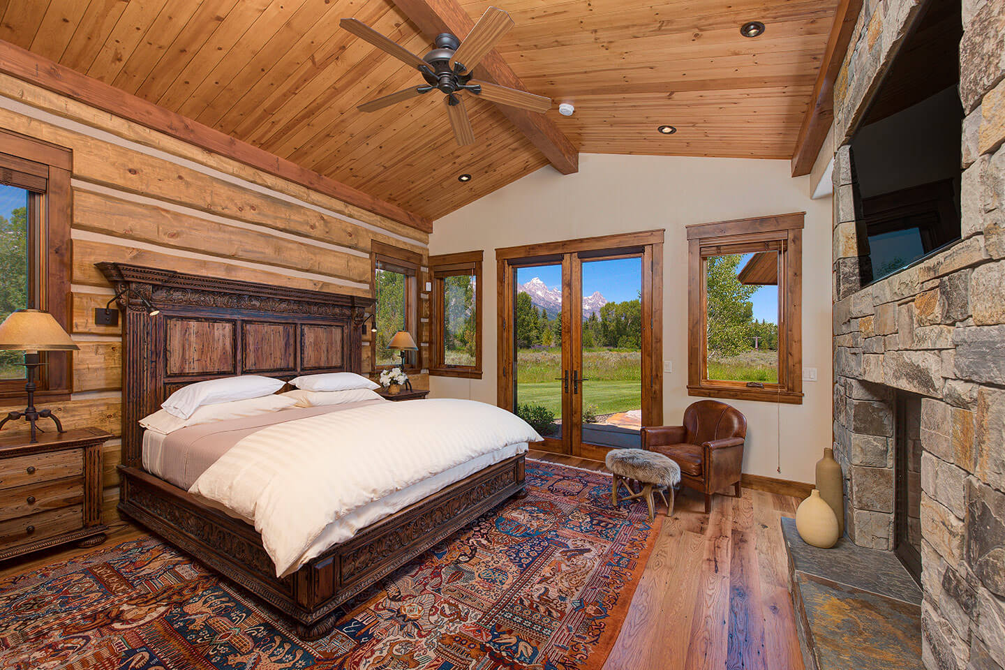 Bedroom with a variety of woods, and native stone fireplace