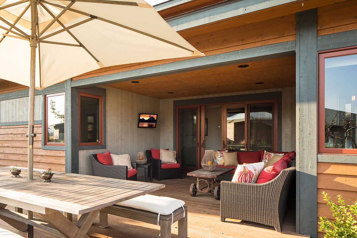 Patio with colorful furnishing, table and umbrella, and tv