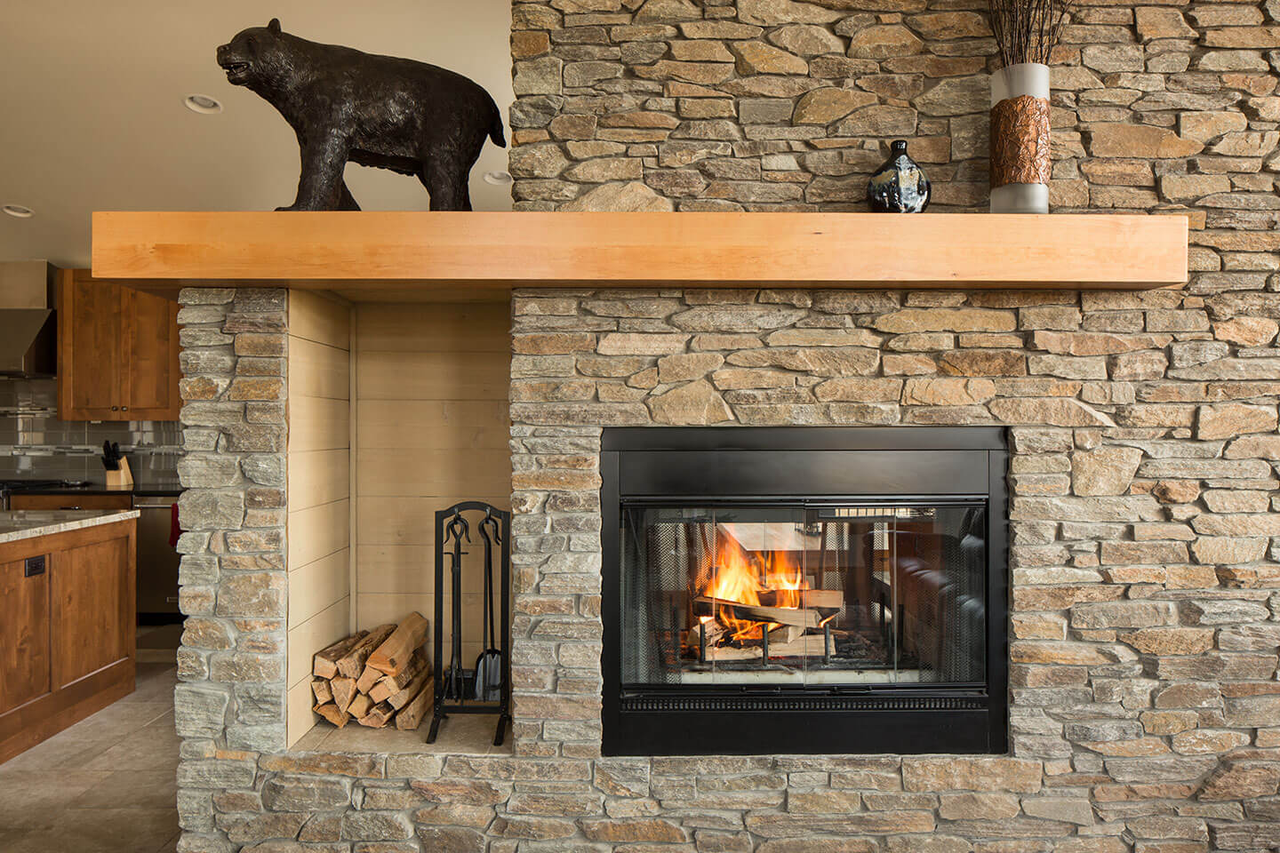 Montana moss rock around enclosed fireplace - black bear statue