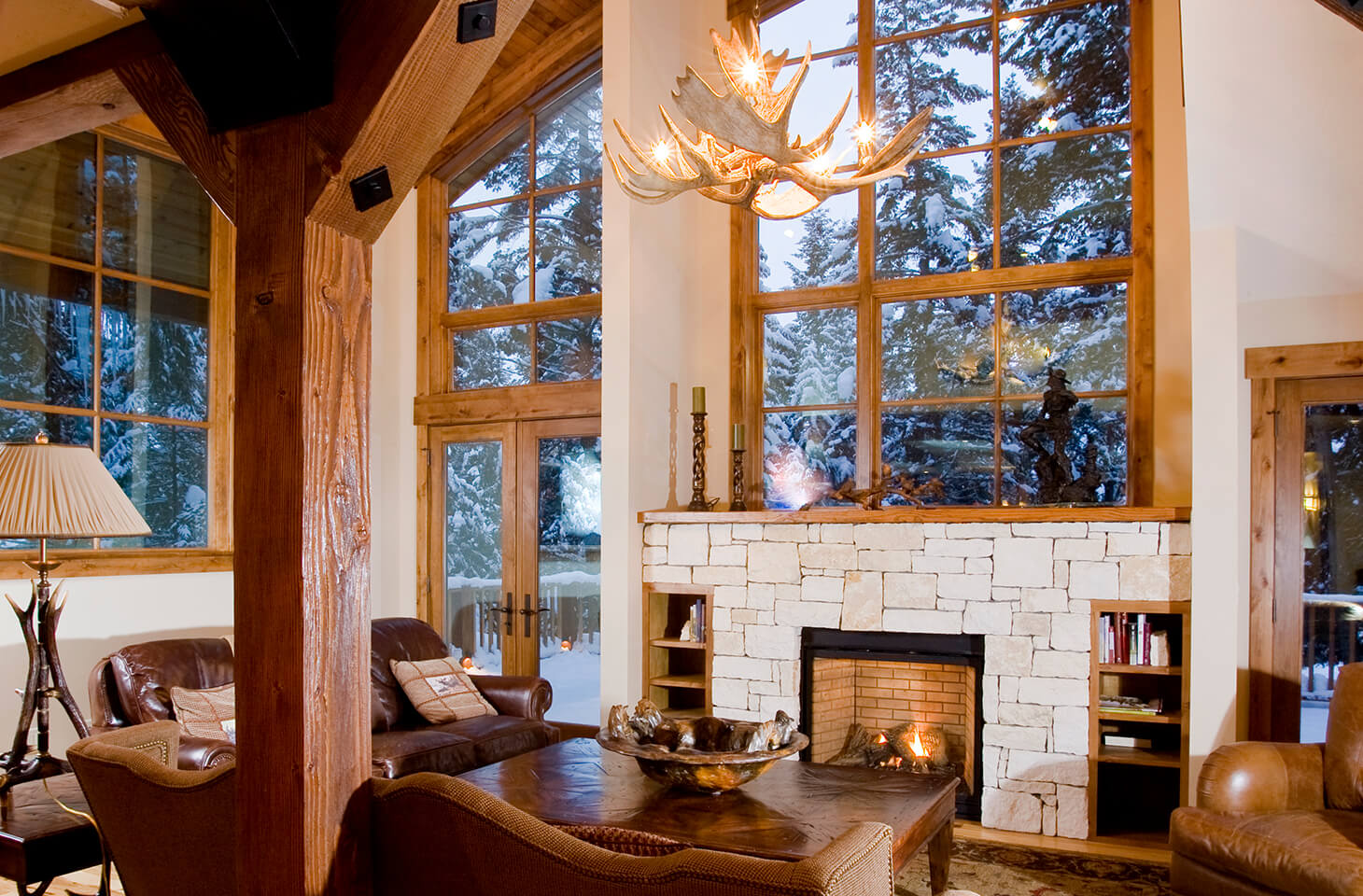 Living room with antler chandelier and open hearth fireplace