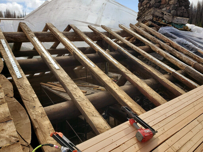 The roof repairs and improvements, with new rafters being installed. These rafters were just harvested and cut from the forest surrounding the lodge, in accordance with the original building making. Image © Brooks Lake Lodge owner.