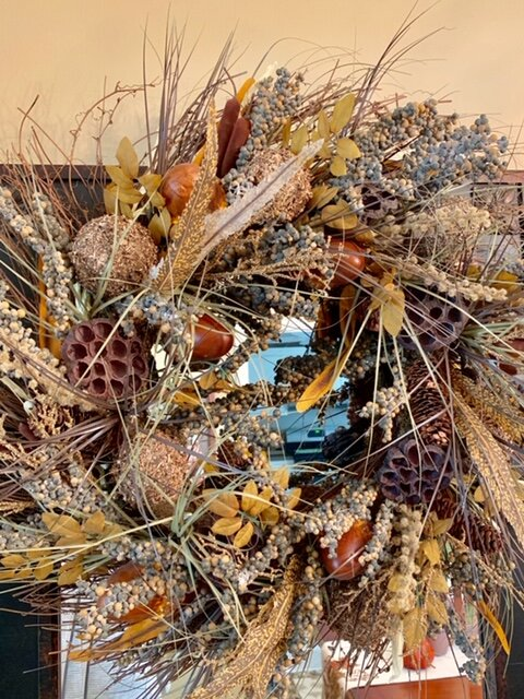 Joan's wreath has lots of texture and color, with silk leaves and dried grasses and seed pods.