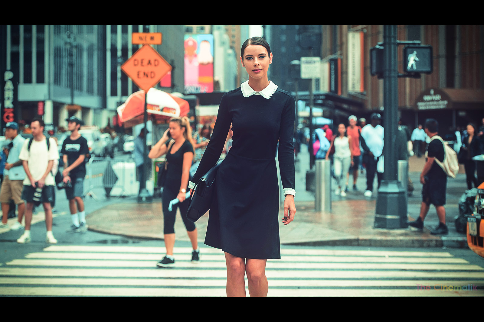 Beautiful model in tight black dress crossing the street at New York Fashion Week cinematic photograph by Kamal Lahmadi/THE CINEMATIK