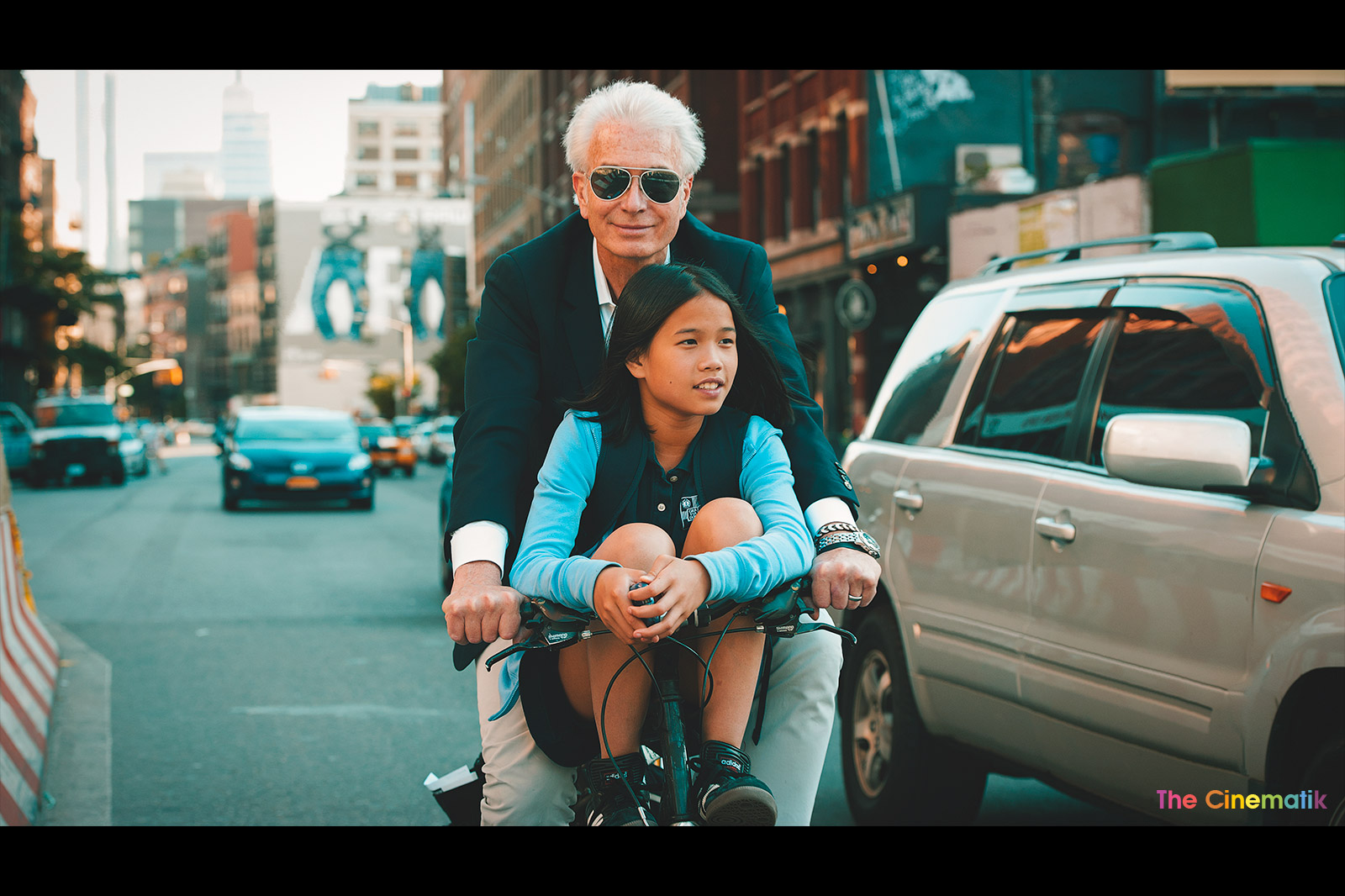 White Grandpa carrying his cute asian granddaughter on his bike in New York cinematic photograph by Kamal Lahmadi/THE CINEMATIK
