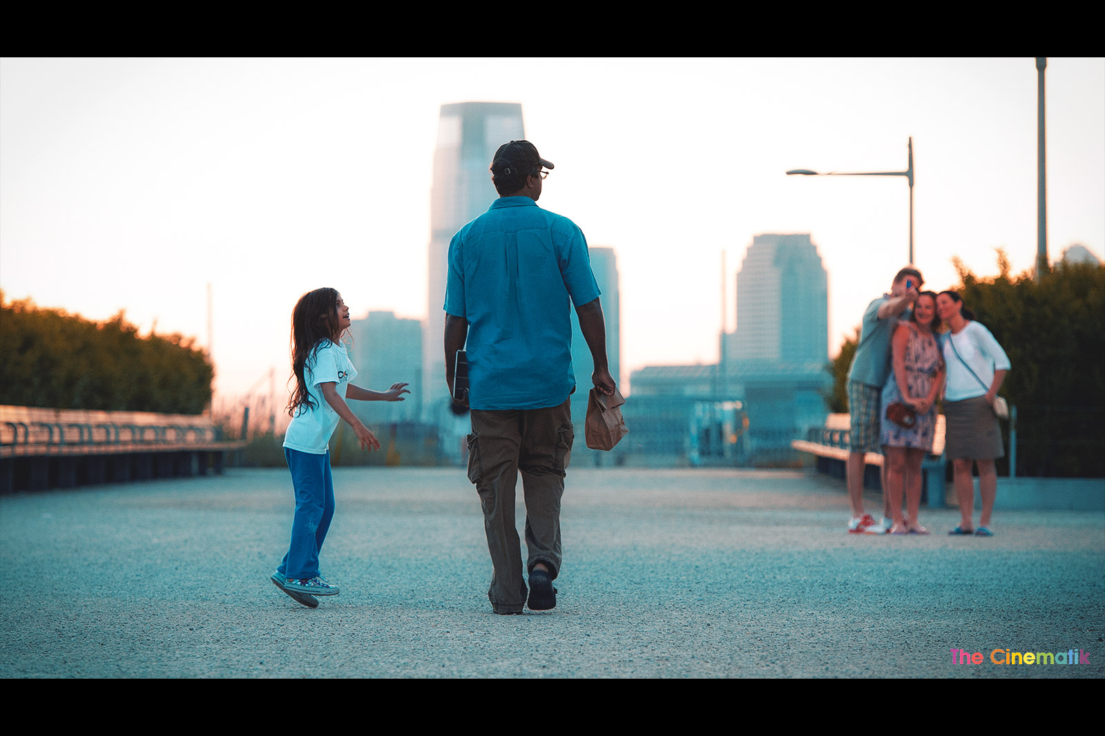 Little girl harassing her tall father in New York sunset cinematic photograph by Kamal Lahmadi/THE CINEMATIK