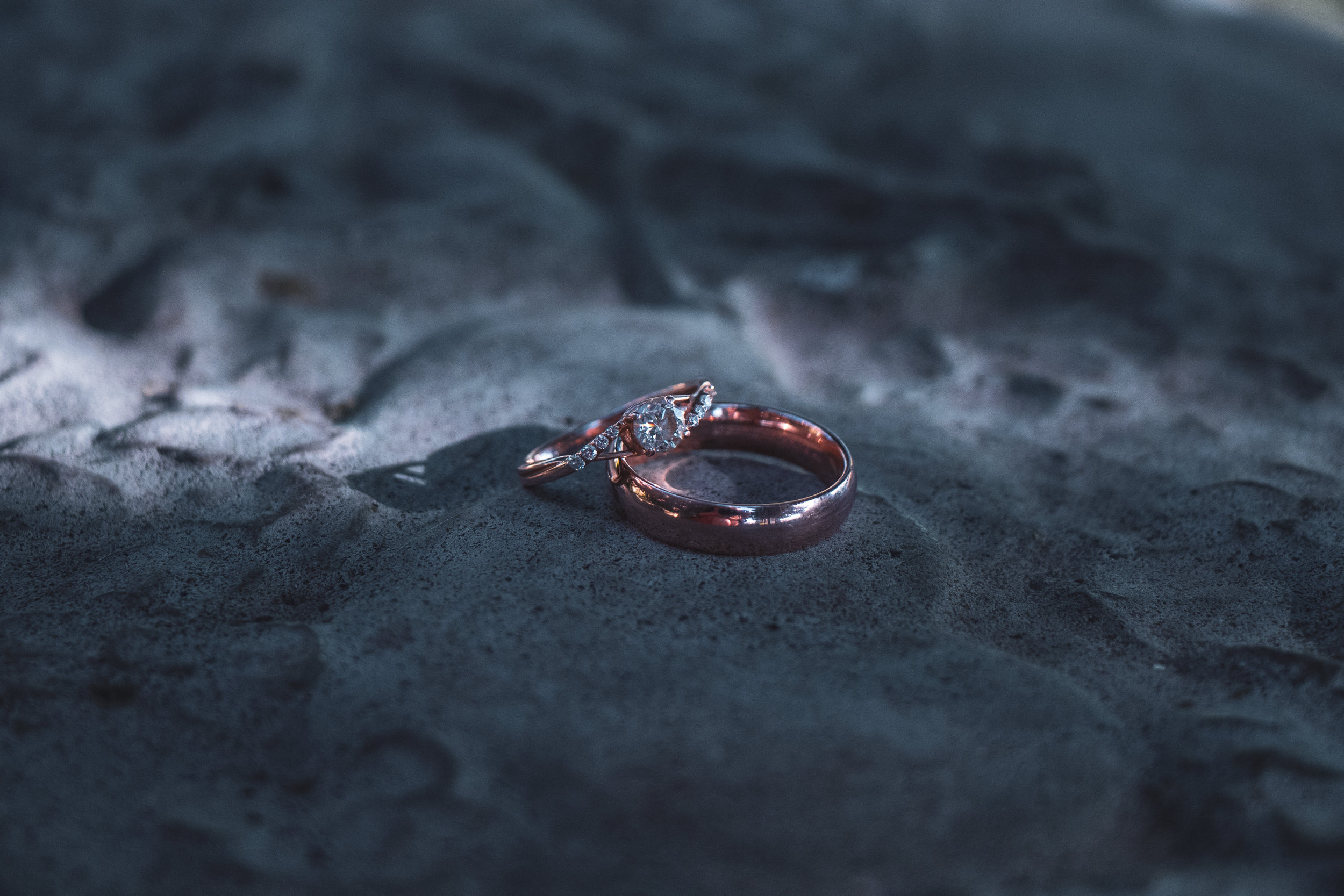 Wedding rings on a cool, stone bench