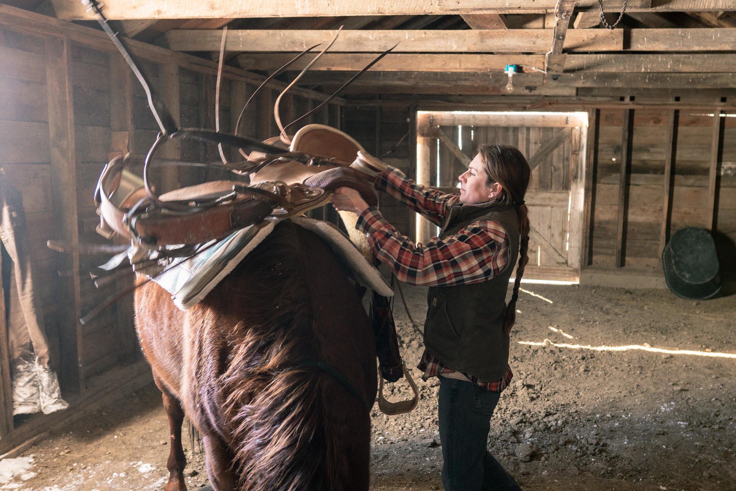 Jenna Flatgard saddling her horse in her barn in eastern Montana.