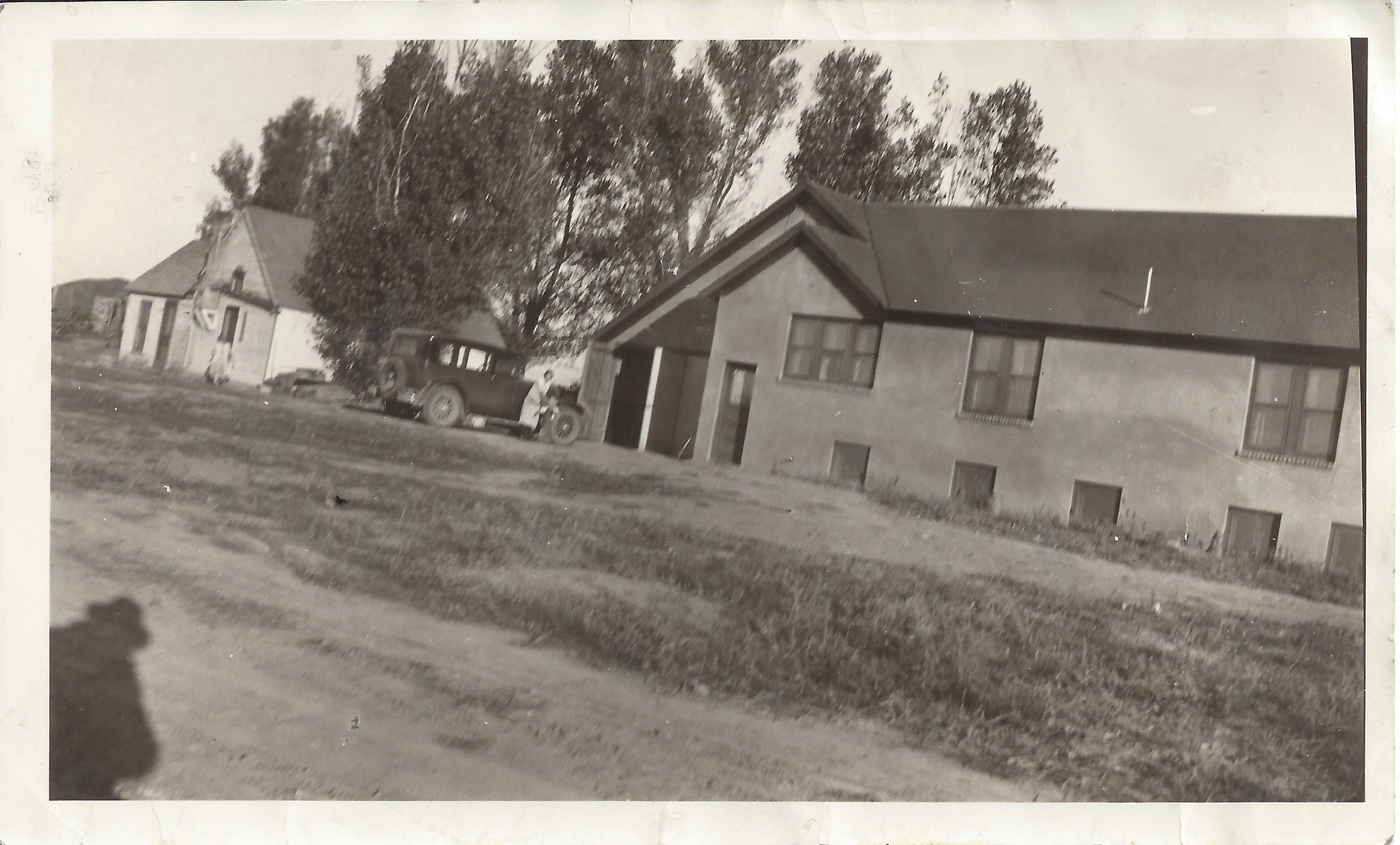 View of the south side of the stucco farm house with the old house still remaining to the west. Mabel and Wally Firestien by the car.