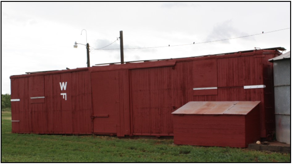 View of the railroad boxcar from the northeast corner with livestock brand.