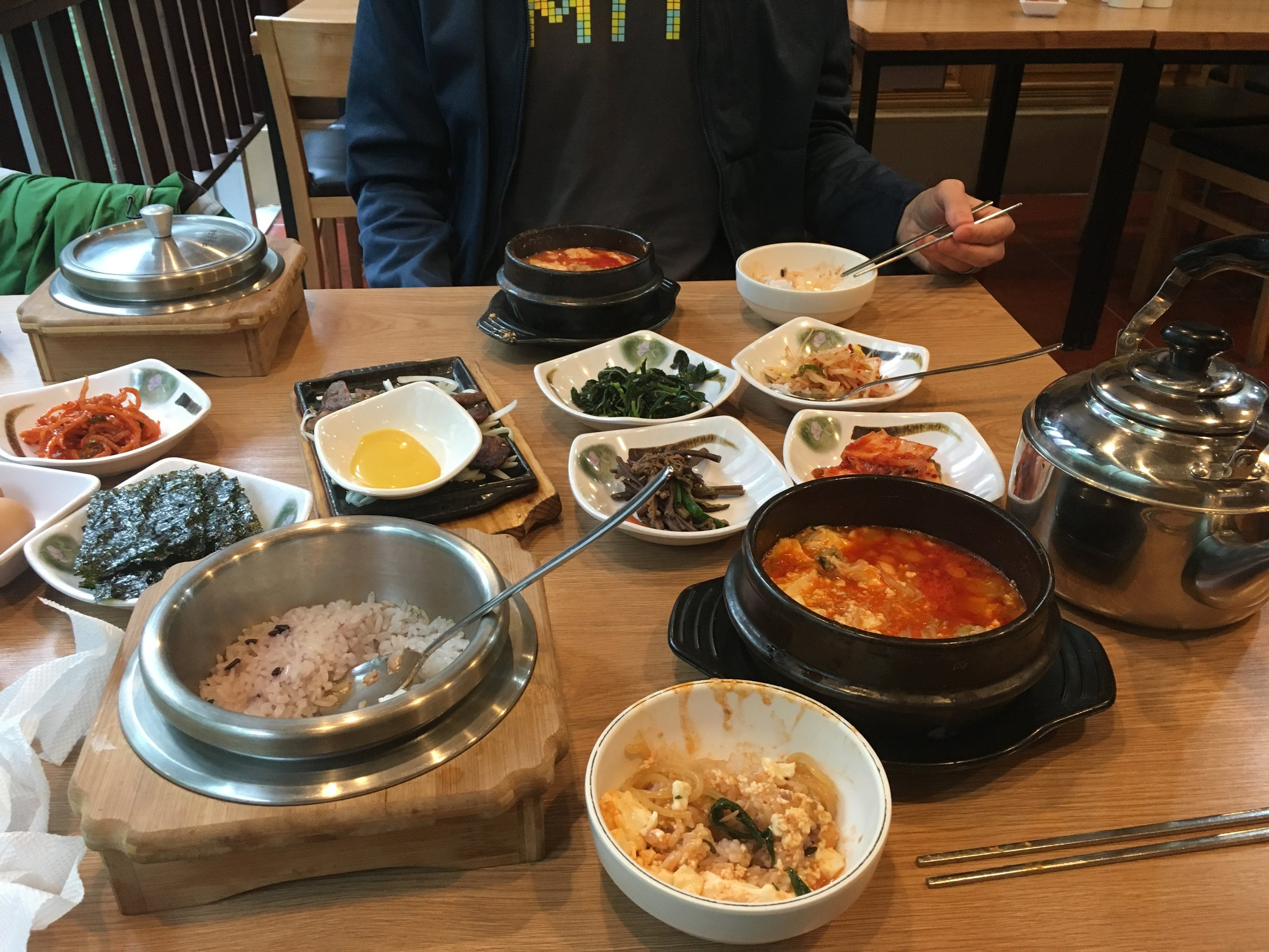 Traditional Korean meal with small pot of veggies and meat, steamed rice, and lots of sides