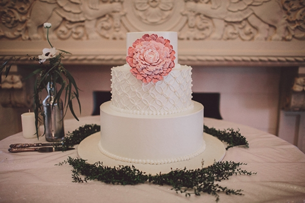 Simple white wedding cake with pink flower