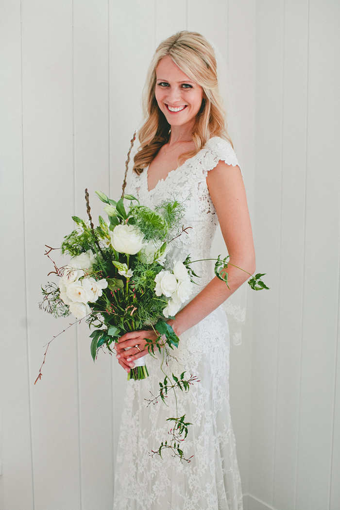 White and green wedding bouquet. Bride in a gorgeous lace dress