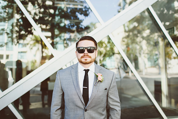 Fun photo idea of the groom. Love his gray suit and black tie!