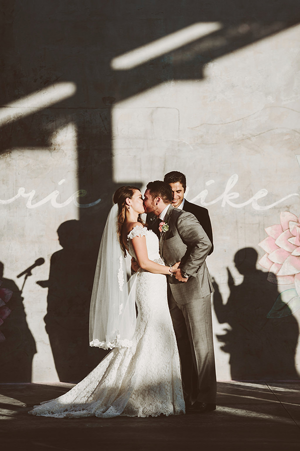 Beautiful photo of the first kiss at a modern whimsical museum wedding ceremony