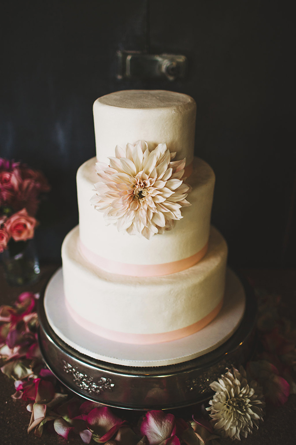 Beautiful simple white and pink wedding cake with a statement flower