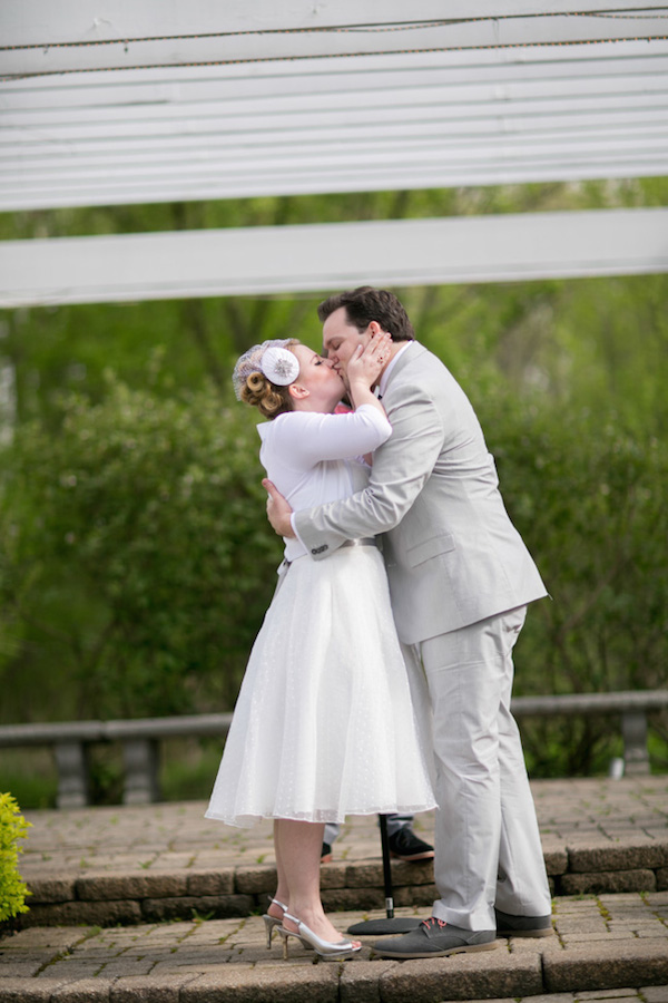 First kiss as a married couple for this adorable bride and groom at their 50's vintage garden party themed wedding!