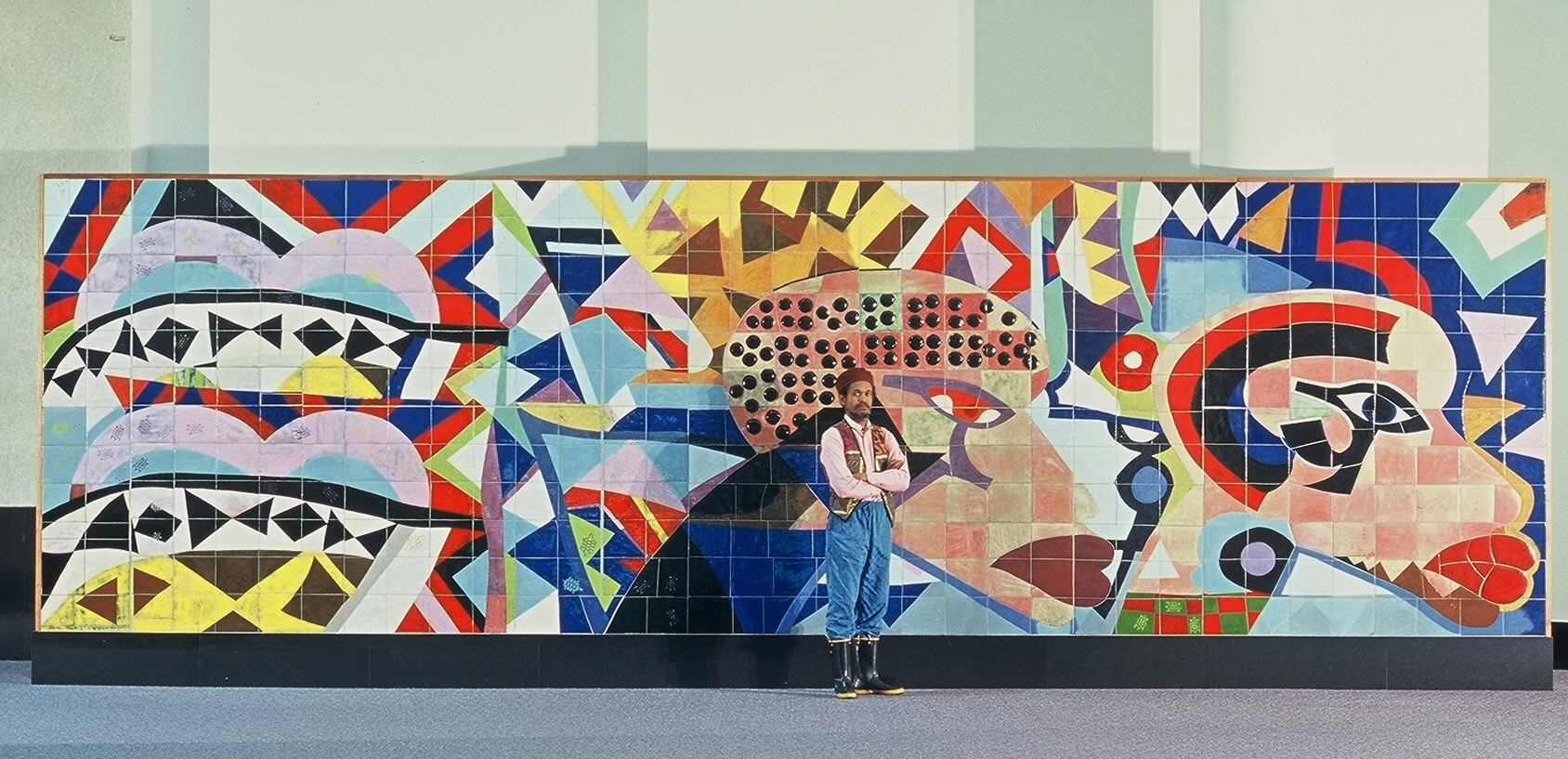 jones-henderson is pictured above with one of his many public art pieces,  procession of the ancestors , in the providence rhode island convention center.
