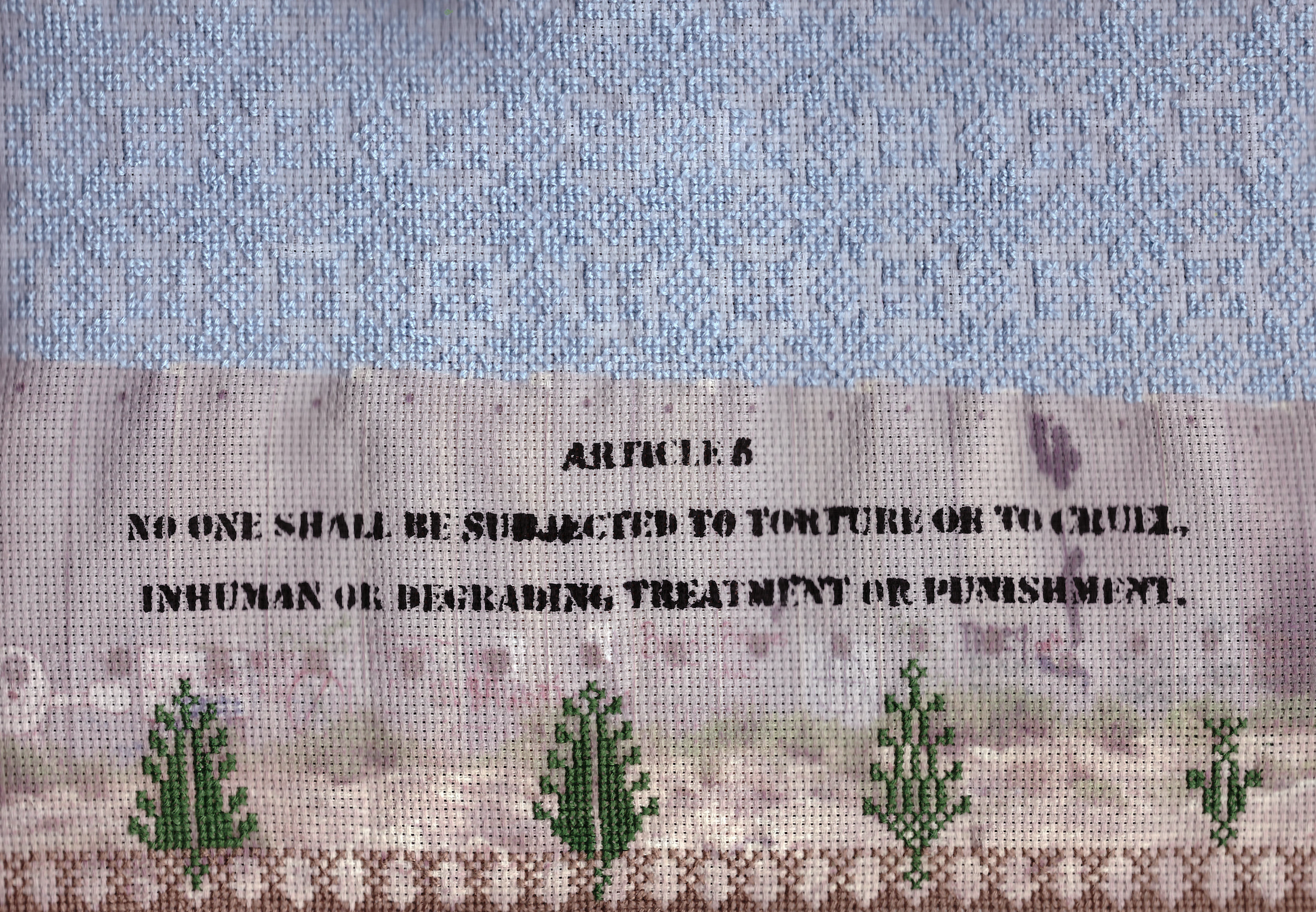 """ARTICLE 5  mixed media on embroidery fabric  """"No one shall be subjected to torture or to cruel, inhuman or degrading treatment or punishment.""""  This is my block in the UDHR Quilt project led by Tal Fitzpatrick and Stephanie Dunlap to celebrate the Universal Declaration of Human Rights and promote awareness of violations happening all over the world. On my block of the quilt, I have hand embroidered the traditional Palestinian motif of the star of Bethlehem across the sky. Article 5 is stenciled on the separation wall representing the significance of graffiti and street art as a tool of communication in the public sphere in Palestine. More traditional Palestinian embroidery, such as Cyprus trees and 'the walls of Jerusalem' motifs run along the bottom of the panel under the wall representing the Palestinian land. Although Israel fails to comply with most of the articles of the Universal Declaration of Human rights, the violation of Article 5 is a succinct summation of the Israeli occupation of the Palestinian people on their native land since 1948.  Now on view at the Museum of Australian Democracy. It is included on one of the four quilts of the """"The #UDHRquilt Project: Craftivism, Quilts & Human Rights"""" exhibition.   https://quilts.moadoph.gov.au    http://talfitzpatrick.com/udhr-craftivism-project"""