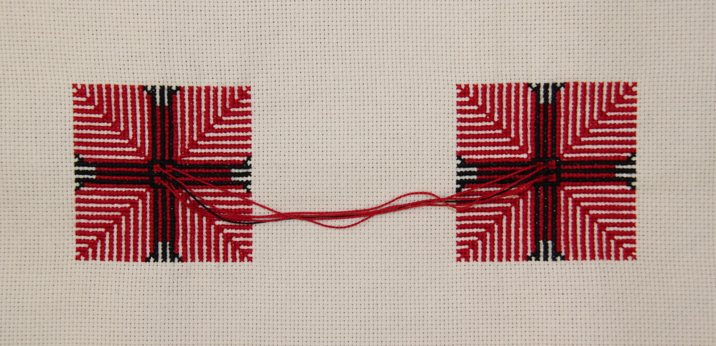 ENTANGLEMENT  Cotton thread on cotton fabric. 15 x 30 cm.  Through the medium of Palestinian cross-stitch hand embroidery, two identical yet separate motifs are joined to represent the concept of entanglement. The theory of quantum entanglement states that even if two particles are physically separated, they can still be connected. Karmic entanglement also speaks of the connection, regardless of space or time, between individuals, an individual to a group of people, or an individual to a belief. In this piece, traditional rules of the symbolic language of Palestinian embroidery are broken and a new translation of the motif is formulated. By understanding entanglement in visual or symbolic terms, an opportunity is created to consider the connecting force or frequency and recognise it as love. Threads emerge from and connect to the four squares centred in each motif, resembling the four chambers of the heart, removing the illusion of separateness while leaving behind the ultimate essence of oneness.