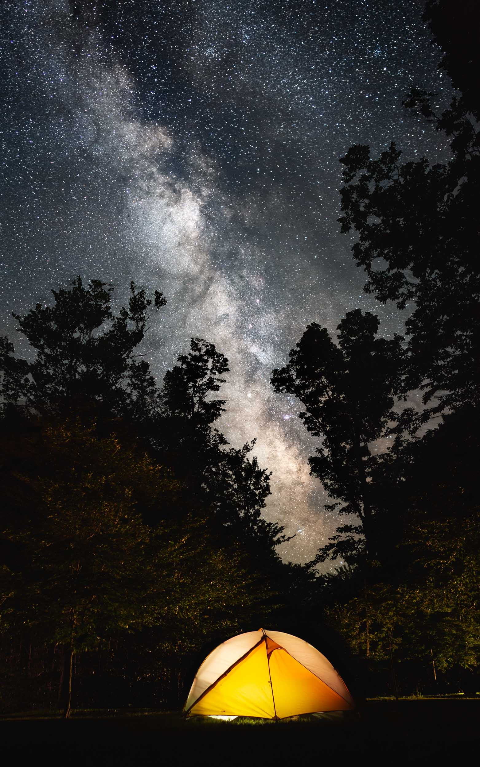 An illuminated tent on a campsite in Cherry Springs State Park in northern Central Pennsylvania, an official Dark Sky site where stars are perfectly visible as well as the Milky Way.