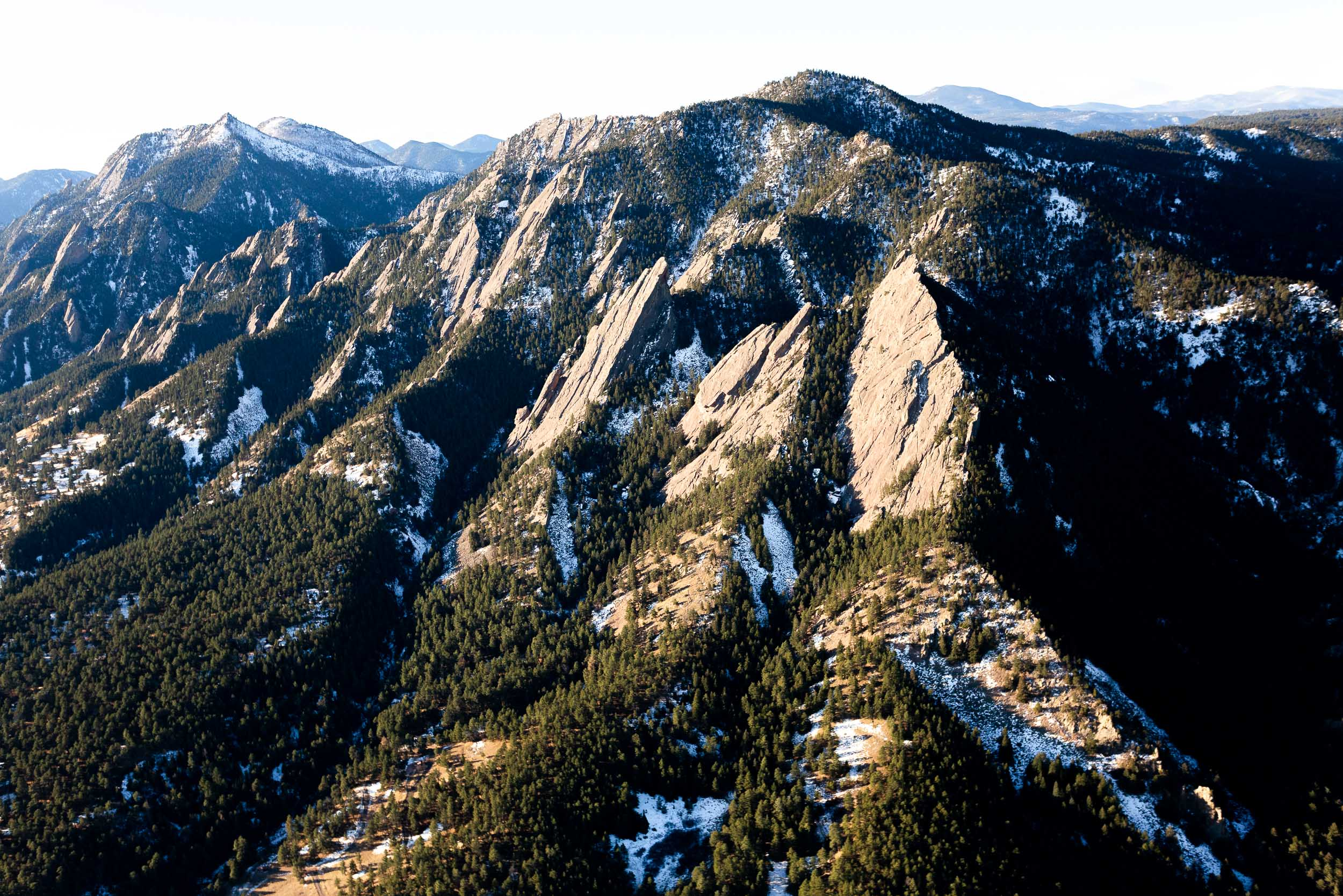 An aerial photo of the Flatirons in Boulder, Colorado in the early morning hours just after sunrise on a November winter morning with some light snow cover.
