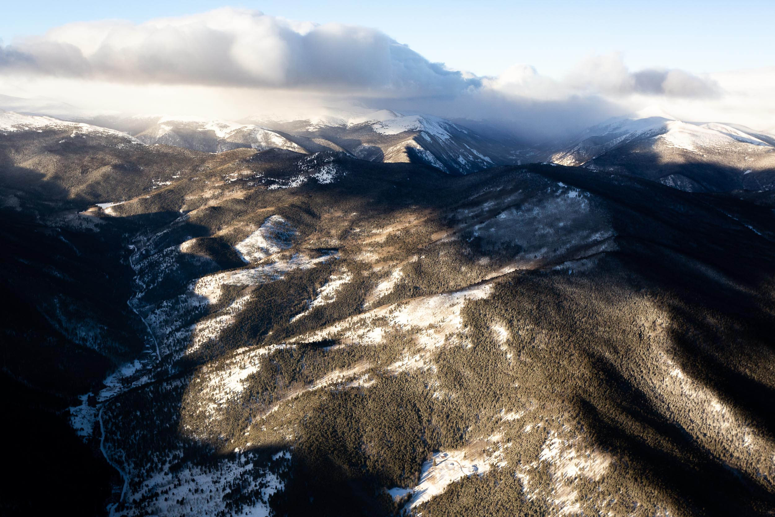 An aerial photography of the Rocky Mountains in Colorado near Mt. Evans with clouds in the sky casting shadows in the valleys below.