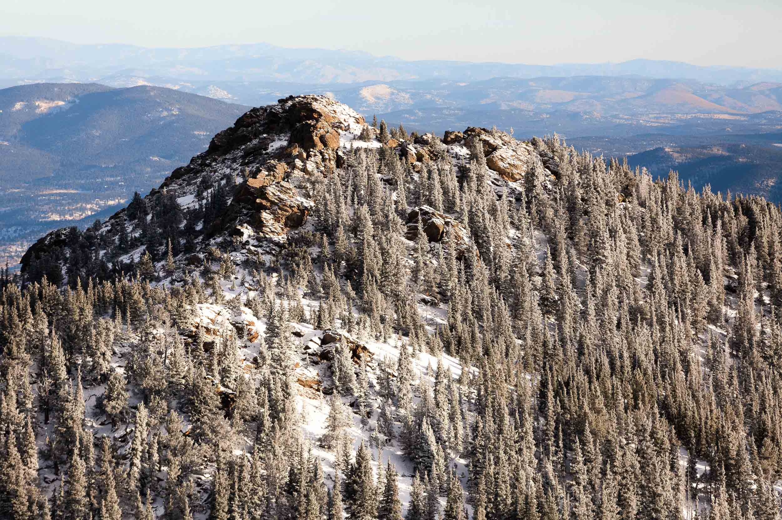 An aerial photography of a snowy peak in the Foothills of the Rocky Mountains near Boulder, Colorado.