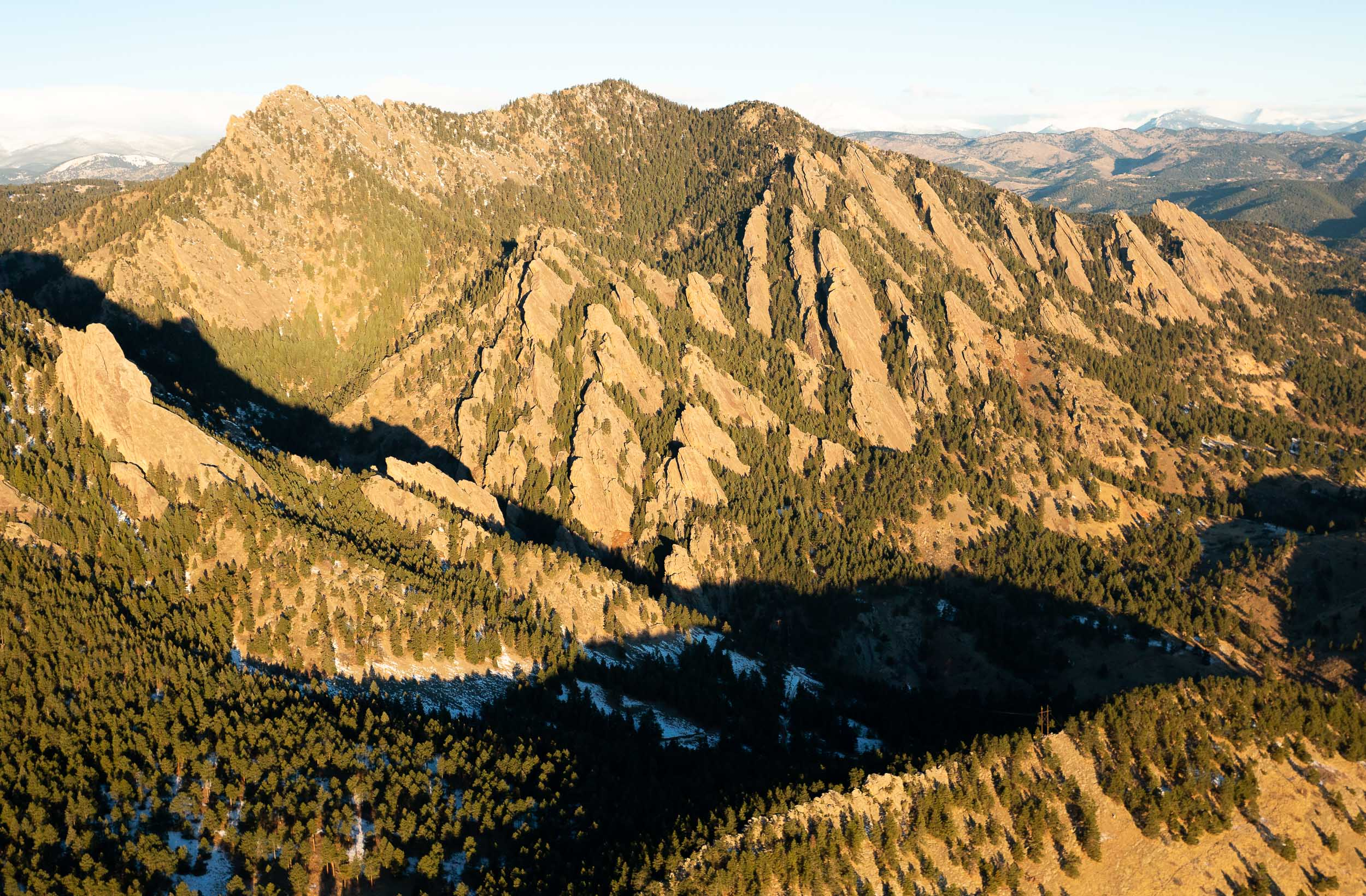 An aerial photography of the Flatirons in Boulder, Colorado, in the Rocky Mountains during the early morning hours just after sunrise with a little bit of snow on the ground.