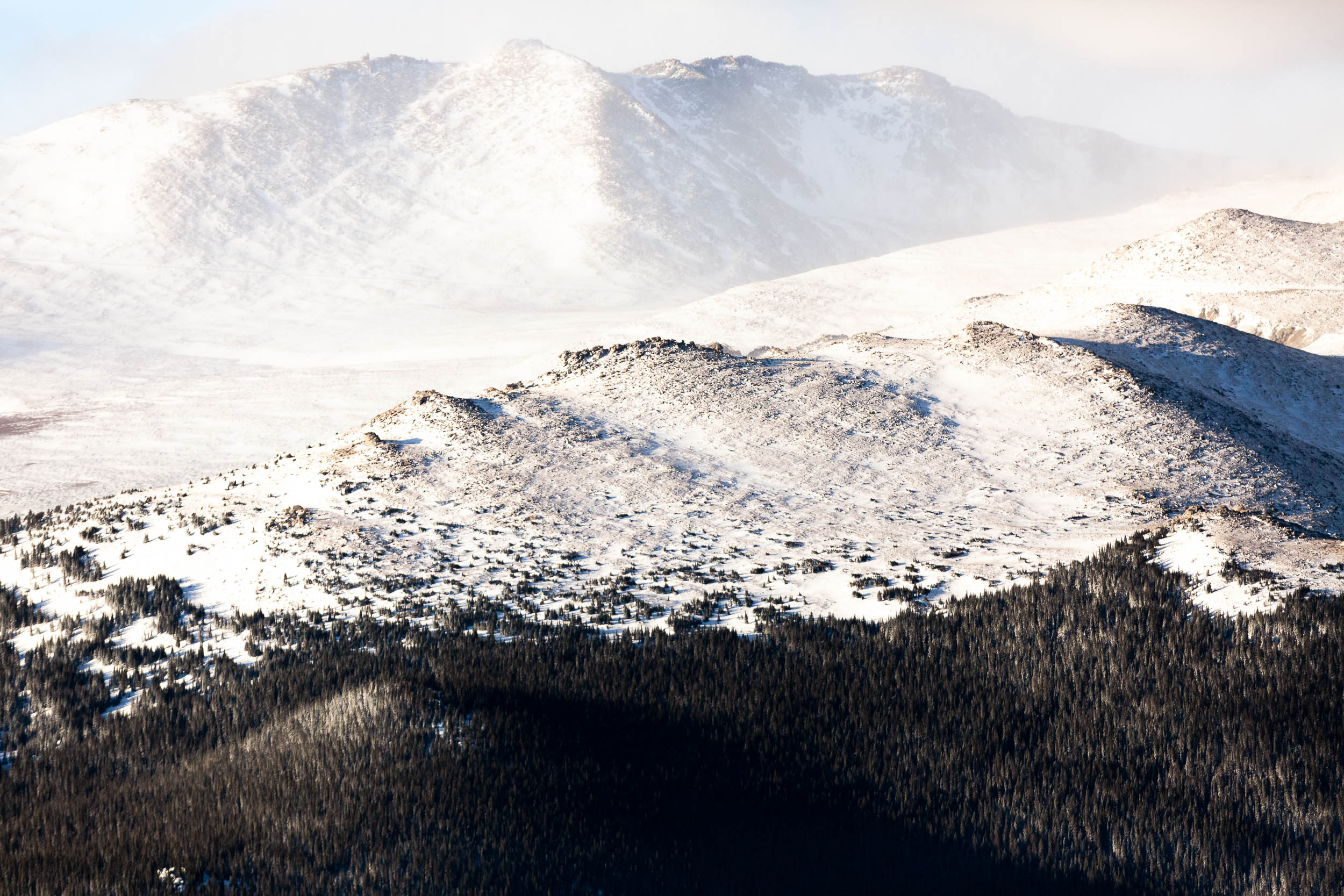 An aerial photograph of the snow-covered mountain range near Mt. Evans in Colorado's Rocky Mountains during winter.